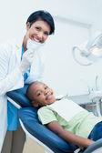 Portrait of smiling female dentist examining boys teeth — Stock Photo
