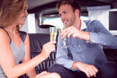 Happy couple drinking champagne in limousine — Stock Photo