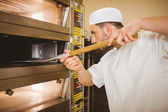 Baker taking bread out of oven — Stock Photo