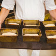 Baker holding tray of loaf tins — Stock Photo #65290753