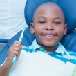 Boy holding toothbrush in the dentists chair — Stock Photo #65291223