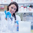 Smiling female scientist using a pipette — Stock Photo #65291369