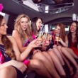Happy friends drinking champagne in limousine — Stock Photo #65292673