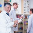 Smiling pharmacist in lab coat writing a prescription — Stockfoto #65293195