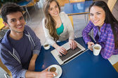 Young students doing assignment on laptop together — Stock Photo