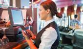 Focused barmaid using touchscreen till  — Stock Photo