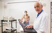 Doktor Dirigieren Fitnesstest lächelnd in die Kamera — Stockfoto