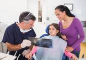 Pediatric dentist explaining to young patient — Stock Photo