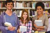 Students standing and smiling at camera holding books — Stock Photo