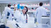 Chemist raising beaker of blue liquid with colleagues behind — Stock Photo