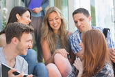 Happy students looking at book outside on campus — Stock Photo