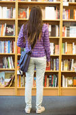 University student standing in the bookcase — Stock Photo