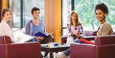 Étudiants assis sur le canapé, réviser et souriant à la caméra — Photo