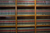 Volumes of books on bookshelf in library — Stock Photo