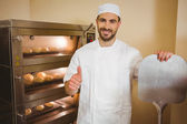 Baker smiling at camera beside oven — Stock Photo