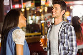 Smiling friends talking and drinking beer and mixed drink — Stock Photo