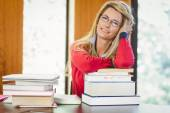 Smiling mature student with stack of books — Stock Photo