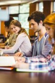 Student looking at camera while studying with classmates — Stock Photo