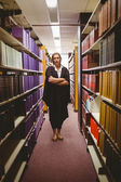 Stern lawyer standing between shelfs with arms crossed — Stockfoto