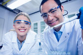 Science students using pipette to fill beaker — Stock Photo