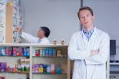 Unsmiling pharmacist standing with arms crossed — Stock Photo