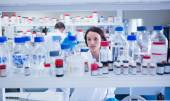 Young chemist picking up the bottles on the shelf — Stock Photo