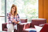 Happy student sitting on couch writing smiling at camera — Stock Photo
