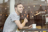 Smiling student sitting with a hot drink — Stock Photo