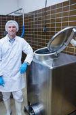Smiling biologist leaning against storage tank — Stock Photo