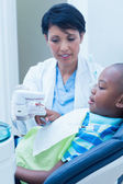 Dentist showing boy prosthesis teeth — Stock Photo