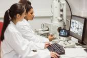 Science students looking at microscopic image on computer — Stock Photo