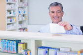 Pharmacist with grey hair holding a prescription — Stock Photo