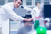Science student working with microscope in the lab — Stock Photo