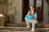 Smiling student sitting and holding book — Stockfoto