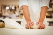Baker kneading dough at a counter — Stock Photo