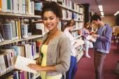 Happy student taking book from shelf — Stock Photo