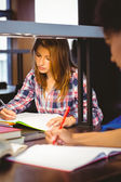 Student sitting at desk writing in notepad — Stok fotoğraf