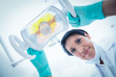 Low angle of female dentist adjusting light — Stock Photo