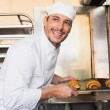 Happy baker taking out fresh croissants — Stock Photo #65536141
