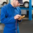 Mechanic using a diagnostic tool — Stock Photo #65537447