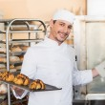 Smiling baker holding trays of croissants — Stock Photo #65538277