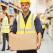 Warehouse worker smiling at camera carrying a box — Stock Photo #65538557