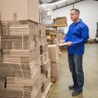 Warehouse worker checking his list — Stock Photo #65538595
