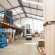 Forklift in a large warehouse — Stock Photo #65538771