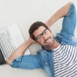 Relaxed businessman lying on his laptop — Stock Photo #65538893