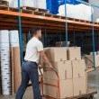 Worker pushing trolley with boxes — Stock Photo #65539555