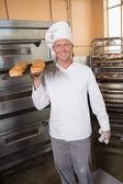 Baker holding tray of fresh bread — Stock Photo