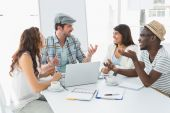Colleagues interacting and using laptop — Stock Photo