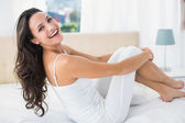 Smiling brunette sitting on bed — Stock Photo