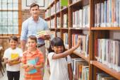 Cute pupils and teacher looking for books in library — Stock Photo